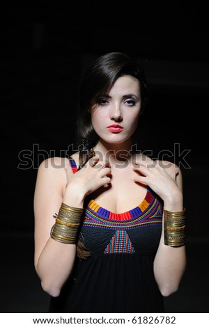 Beautiful model girl with long hair and bright make-up touching her skin - stock photo