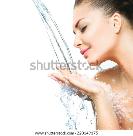 Beautiful Model Girl with splashes of water in her hands. Beautiful Smiling Woman under splash of water with fresh skin over blue background. Skin care Cleansing and moisturizing concept. Beauty face  - stock photo