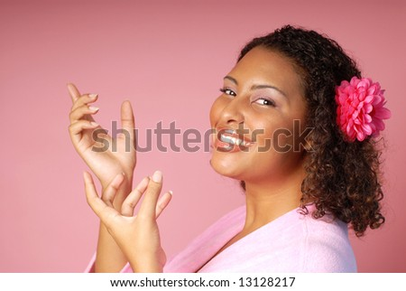 Beautiful model in a bathrobe pointing toward pink copy space - stock photo