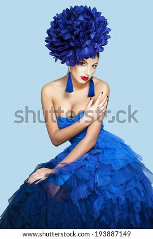 Beautiful model in a blue dress over blue background - stock photo