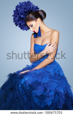 Beautiful model in a blue dress over neutral background - stock photo