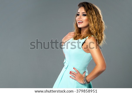 Beautiful model in blue dress posing in studio