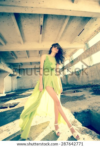 beautiful model in green dress posing in grunge location  - stock photo