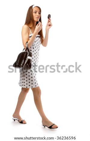 beautiful model in polka-dot dress with black bag does a swift make-up, while walking - stock photo