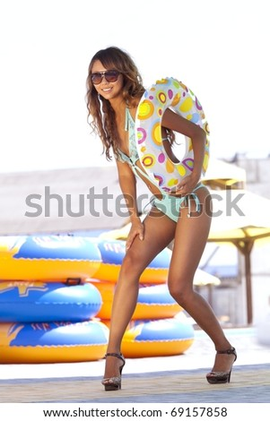 Beautiful model in turquoise swimsuit, with multicolored inflatable ring - stock photo