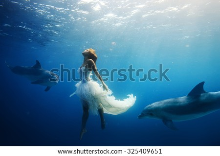 Beautiful model in white dress underwater. A girl diving with dolphins without scuba gear. Fantasy mermaid in deep ocean. Water surface with sunbeams. - stock photo