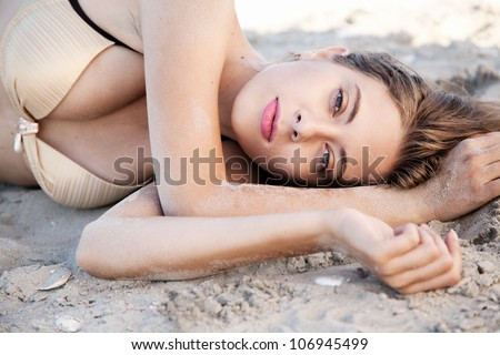 Beautiful model lying in sand on a beach - stock photo