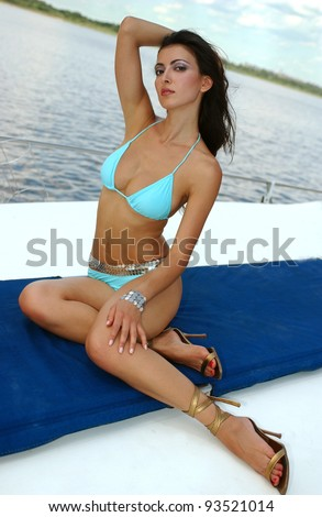 Beautiful model sitting pretty at the deck of motor boat, wearing designer's bikini with water and blue sky at the background - stock photo