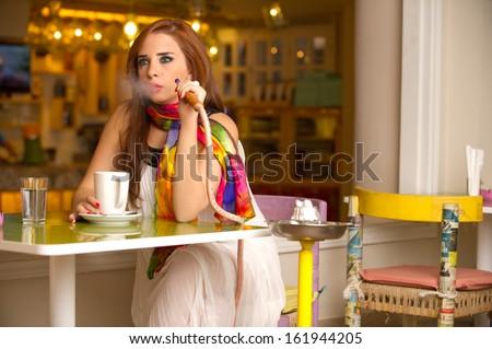 Beautiful model smoking hookah in a cafe - stock photo
