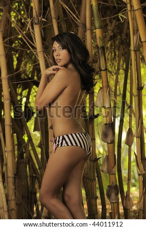 Beautiful model standing in bamboo - stock photo
