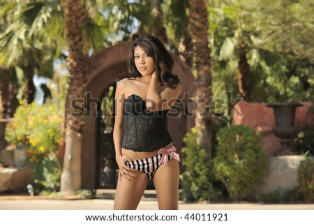 Beautiful model standing in front of desert oasis horizontal. - stock photo