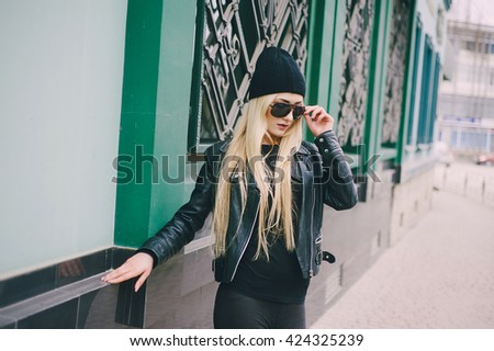 beautiful model walks through the city in a beautiful hat and glasses