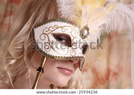 Beautiful model wearing a wedding dress and Venetian mask, studio