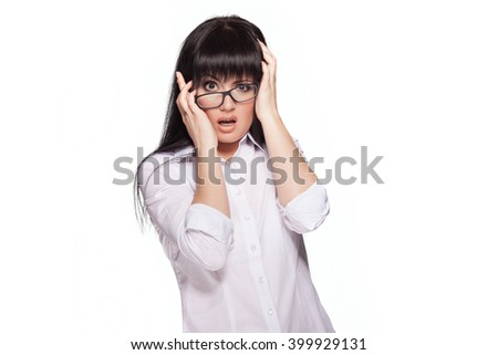 Beautiful model wearing glasses and a white office shirt. Pretty brunette grabs her head in a state of panic. - stock photo
