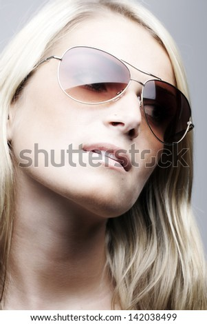 Beautiful model wearing sunglasses isolated on white background.