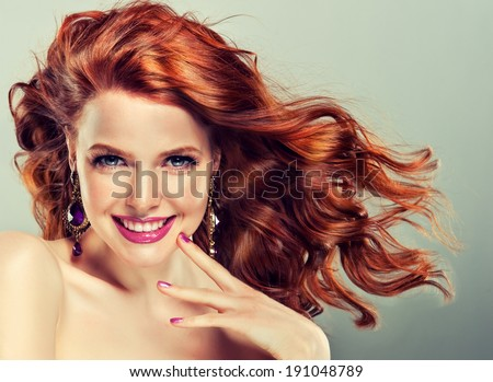 Beautiful model with curly red hair and fashion earrings - stock photo