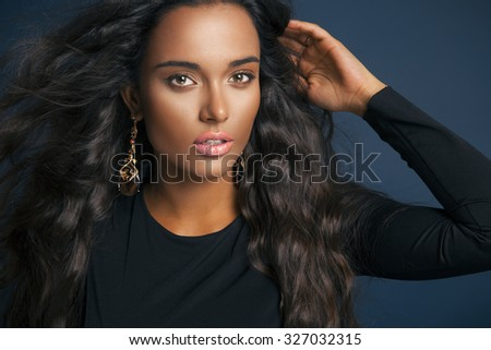 Beautiful model with elegant hairstyle and glamorous jewelry . Attractive woman with fashion wavy hairstyle and colorful makeup over blue background. Studio shot, Horizontal - stock photo