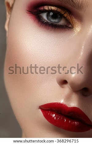 Beautiful model with fashion make-up. Close-up portrait sexy woman with glamour lip gloss makeup and bright eye shadows. Macro shot of celebrate visage, clean skin, lips with red lipstick, eyeshadows. - stock photo