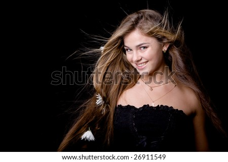 Beautiful model with flowers in her hair smiling on black - stock photo