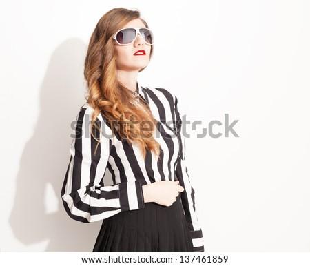 beautiful model with high waisted pleated skirt wearing eyeglasses posing on white background - stock photo