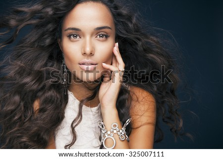 beautiful model with wavy hairstyle and accessories. Portrait of young woman with makeup and fresh skin. Blowing hair. Toned in warm colors. Studio shot, horizontal - stock photo