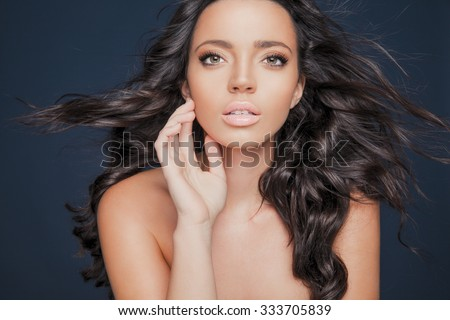 Beautiful model with wavy hairstyle.Portrait of young woman with makeup and clean skin. Toned in warm colors. Studio shot, horizontal - stock photo