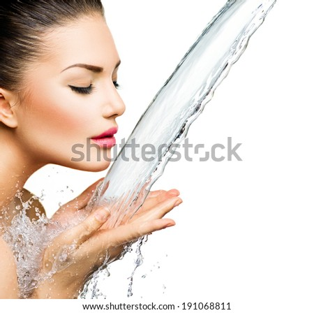Beautiful Model Woman with splashes of water in her hands. Beautiful Smiling girl under splash of water with fresh skin over blue background. Skin care, Cleansing and moisturizing concept. Beauty face - stock photo