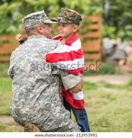 Beautiful modern american family. Father wearing military uniform hugs his son. focus on son - stock photo