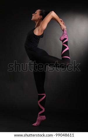 beautiful modern ballet dancer posing on black background - stock photo