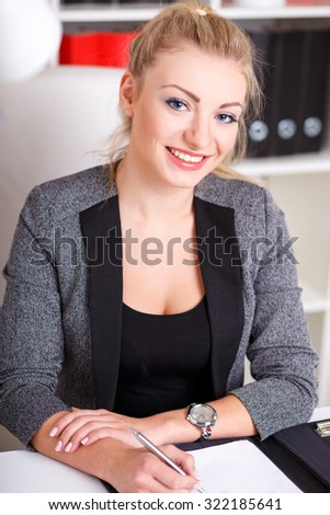 beautiful modern businesswoman in her office with a paper folder and tablet computer and mobile phone - stock photo