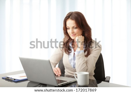 Beautiful modern businesswoman working on her laptop in office. - stock photo