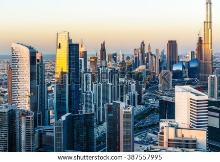 Beautiful modern city architecture at golden sunset. View of Dubai business bay towers.