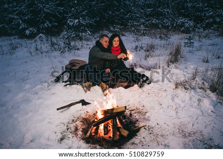 Beautiful Modern Couple in a Winter Forest with Sparklers for Festive Mood. Man Kissing Woman, Woman Smiling. Selective Focus. Close Up Portrait.