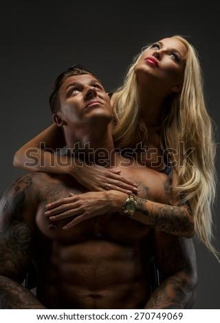 Beautiful modern couple posing in studio - stock photo