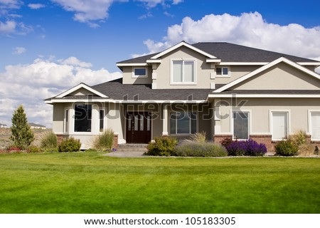 Beautiful modern design house home with blue sky and green grass - stock photo
