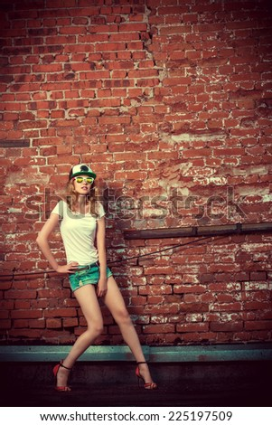 Beautiful modern girl near the brickwall. Youth style. Fashion shot. - stock photo