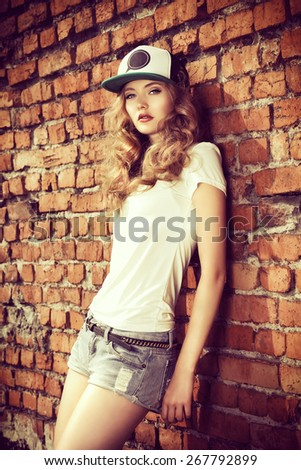 Beautiful modern girl near the brickwall. Youth style. Fashion shot. - stock photo