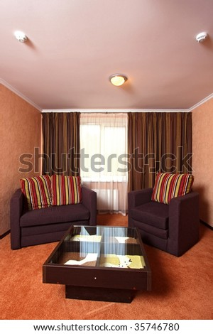 Beautiful modern hall with a sofa, an armchair, and a small little table in the room centre