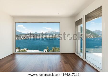 beautiful modern house, empty room with window overlooking the lake - stock photo