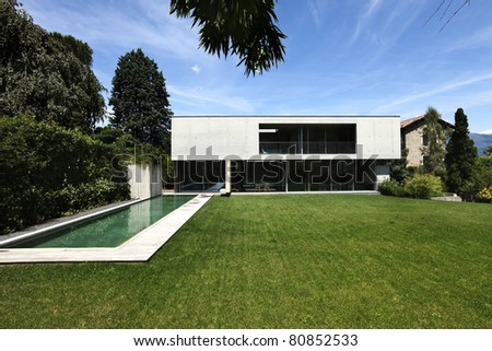 beautiful modern house outdoors, pool and garden view - stock photo