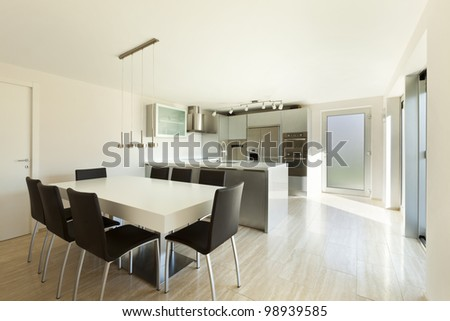 beautiful modern house, view of kitchen with dining table - stock photo