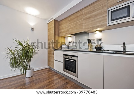 beautiful modern kitchen with built in appliances and wooden surface - stock photo