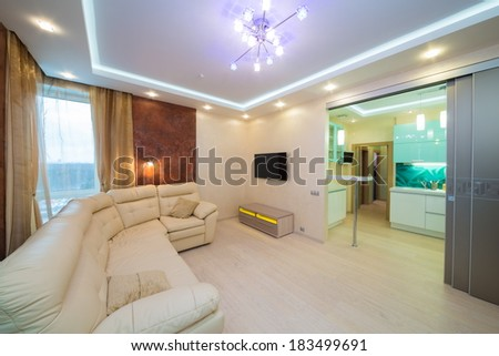 Beautiful modern living room with sofa and TV overlooking the kitchen  - stock photo