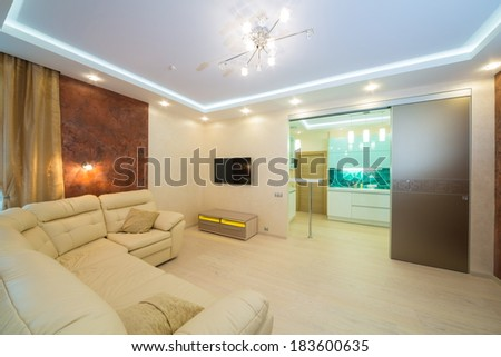 Beautiful modern living room with sofa overlooking the kitchen  - stock photo