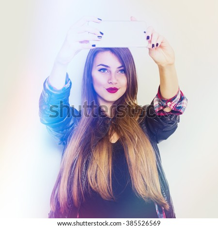 Beautiful modern millennial blonde teenage girl with long blonde hair taking a selfie on smartphone. Cute young woman photographing herself. Retouched, filter, square format. - stock photo
