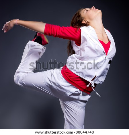 Beautiful modern style female dancer posing in studio - stock photo