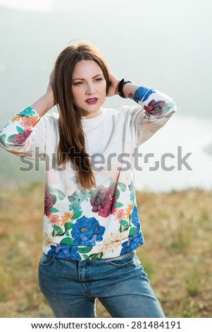 Beautiful modern woman with long hair in a multicolor sweater  outdoors. Smiling girl enjoys fine warm spring weather highly in mountains against the sea - stock photo