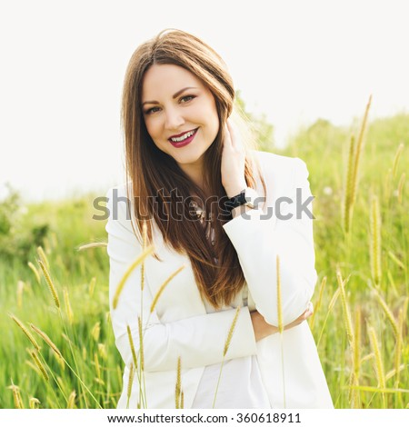 Beautiful modern woman with long hair in a white shirt and blue jeans  outdoors. Smiling girl enjoys fine warm spring weather. Photo with instagram style filters - stock photo