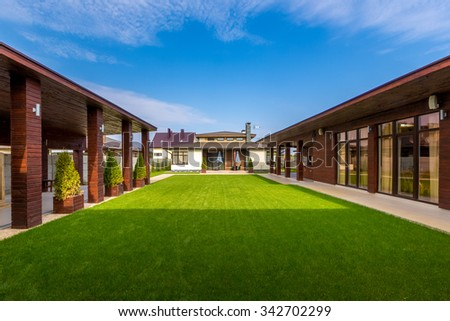 Beautiful  modern wooden house  with stained glass windows, view from the green lawn. - stock photo