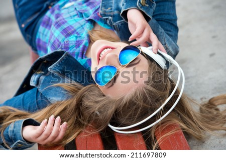 Beautiful modern young woman listening to music with headphones - stock photo